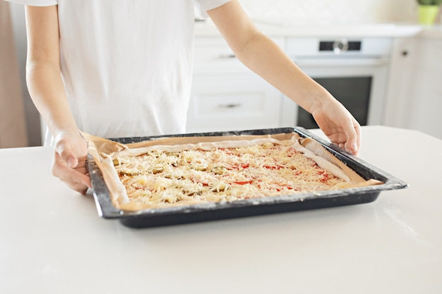 Un niño hace una pizza. salami, queso, salsa de tomate, tomates, pepinos.