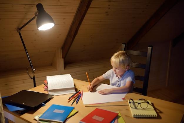 Niño haciendo los deberes, pintando y escribiendo en la noche de hogar. entrenamiento para niños para escribir y leer.
