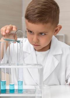 Niño haciendo un experimento científico en la escuela.