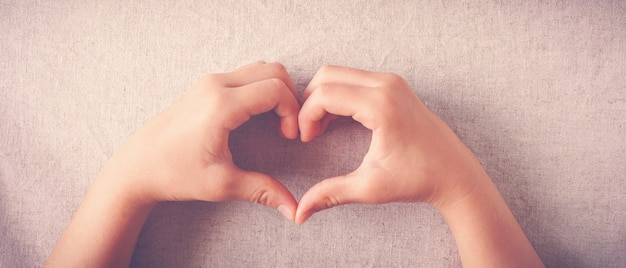 Niño haciendo forma de corazón con las manos