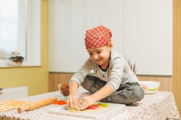 Niño haciendo galletas con moldes de galletas navideñas