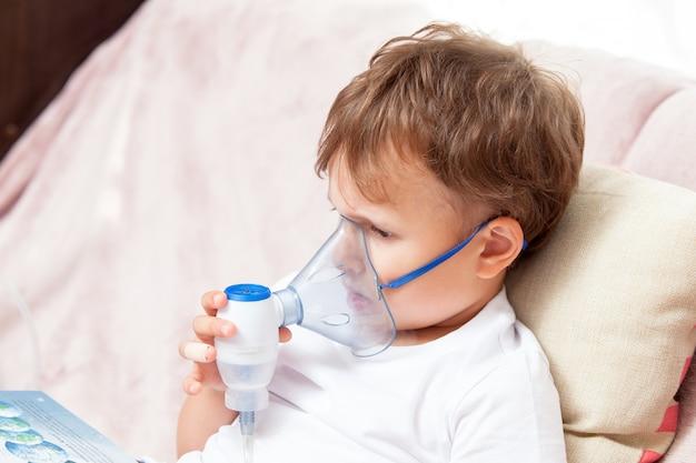 Niño haciendo inhalación con un nebulizador en casa y viendo un libro