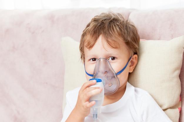 Niño haciendo inhalación con un nebulizador en casa