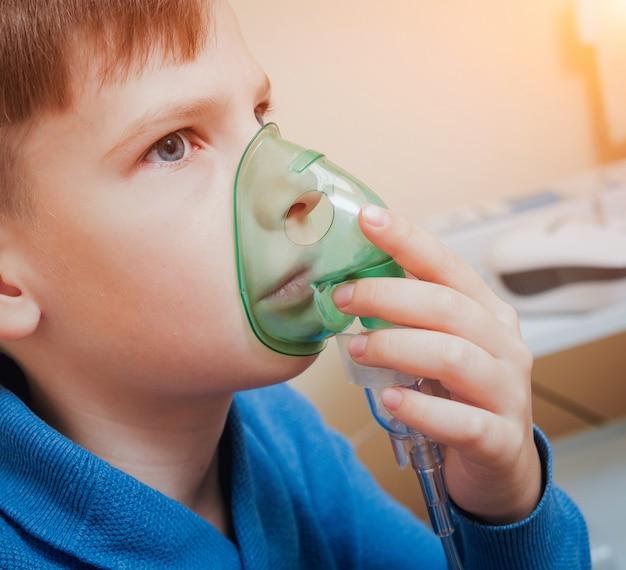 Niño haciendo inhalación con nebulizador en la clínica.
