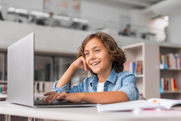 Niño haciendo sus deberes en un portátil en la biblioteca