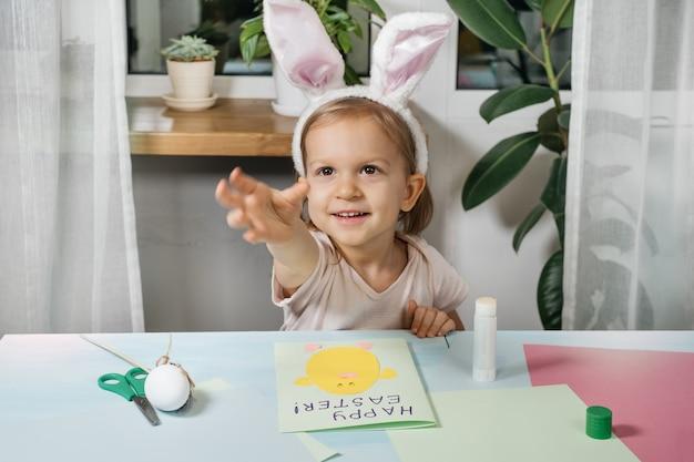 Niño haciendo tarjeta de regalo de huevo de pascua con un conejito de papel en casa. hecho a mano. proyecto de creatividad infantil, manualidades, manualidades para niño, infante.