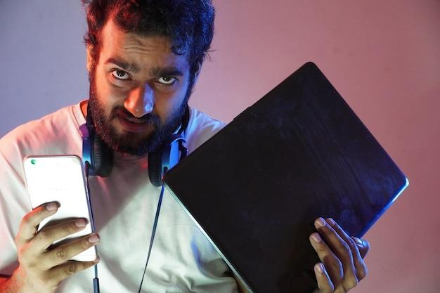 Un niño hacker con portátil y móvil y cara de ira.