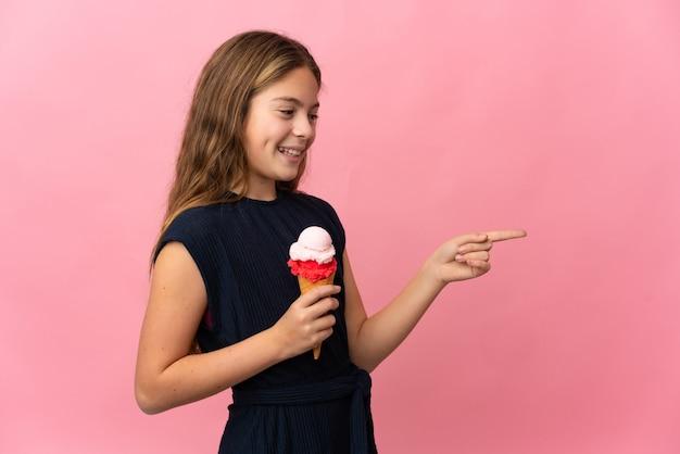 Niño con un helado de cucurucho sobre fondo rosa aislado apuntando con el dedo hacia un lado y presentando un producto
