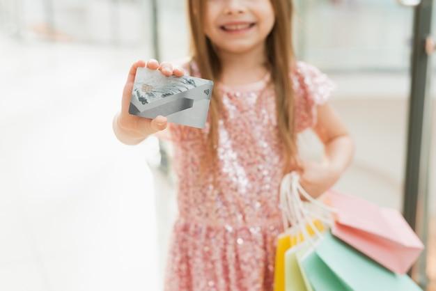 Un niño hermoso en el centro comercial hace compras. concepto de compra en línea. una niña con un vestido rosa con bolsas de colores pastel en sus manos