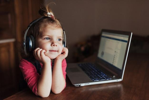Niño hermoso feliz en auriculares escuchando música