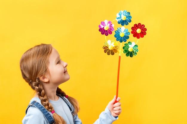 Niño hermoso lindo que sostiene un juguete del molinete
