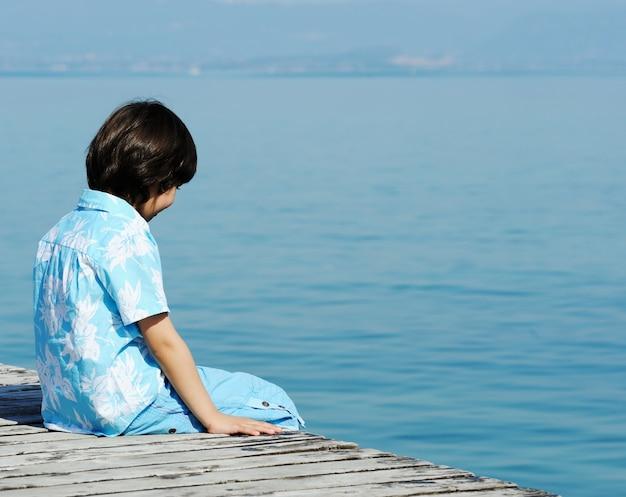 Niño en un hermoso muelle del lago