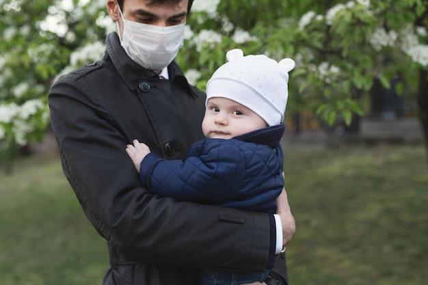 Niño y hombre en máscara protectora médica en la calle