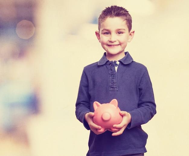 Niño con una hucha Foto gratis