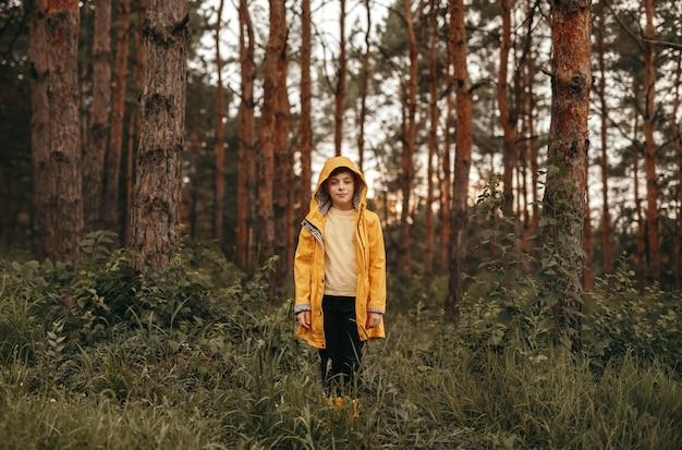 Niño en impermeable en el bosque de verano