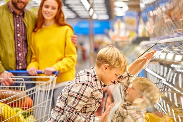 El niño se inclinó en la vitrina del supermercado mientras los padres compran juntos, quiere que los padres compren algo con lo que soñó.