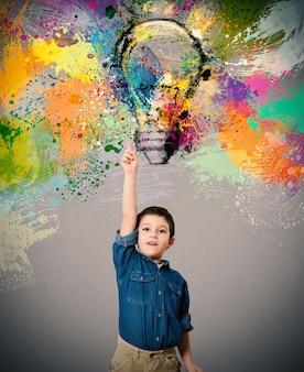 El niño indica una gran bombilla de color diseñada