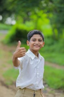Niño indio / asiático mostrando los pulgares para arriba