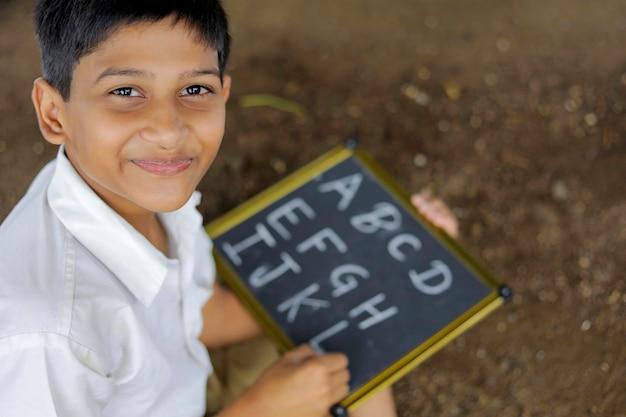 Niño indio escribiendo el alfabeto abcd en la pizarra