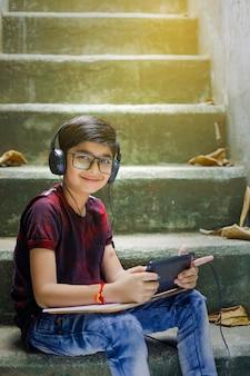 Niño indio estudiando en línea mediante teléfono móvil en casa