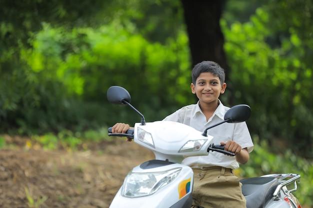 Niño indio montando moto