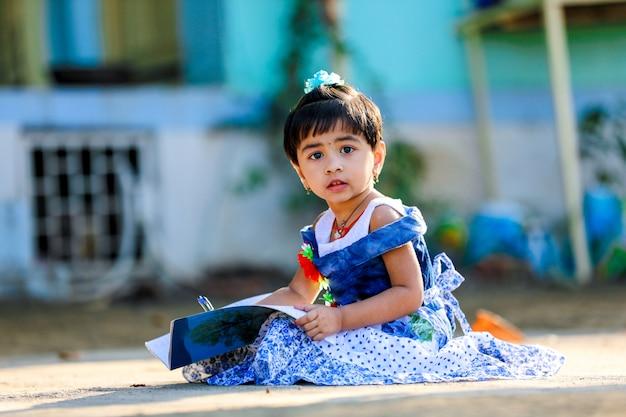 Niño indio de la niña que escribe en el cuaderno, estudiando
