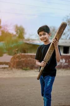 Niño indio rural jugando al cricket