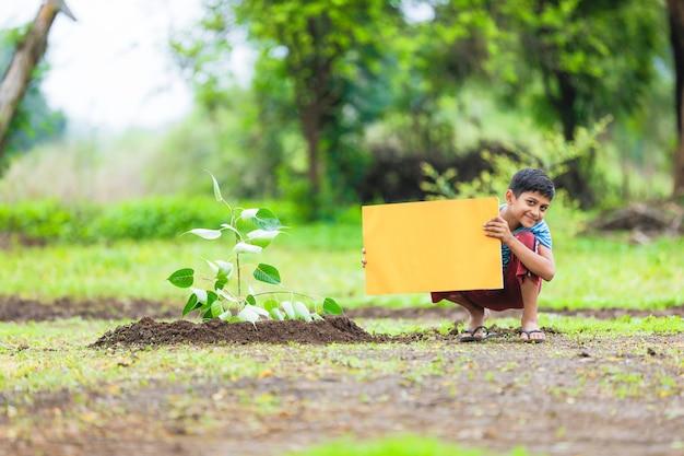 Niño indio sosteniendo el cartel vacío
