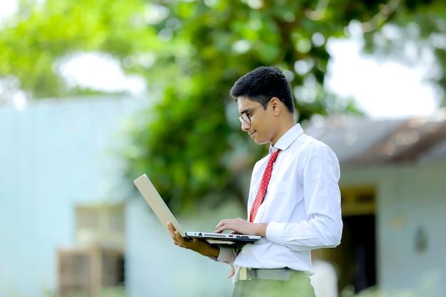 Niño indio usando laptop, concepto de educación en línea