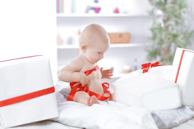 Niño infantil bebé niño niño sentado en presenta regalo para celebración. concepto de navidad año nuevo.