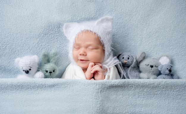 Niño infantil en capó con orejas durmiendo con juguetes
