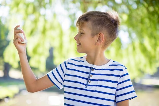 Niño con inhalador para el asma en el parque
