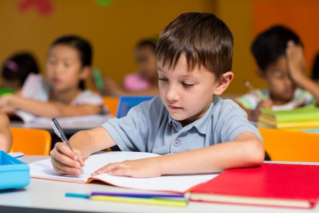 Niño inocente escribiendo en libro