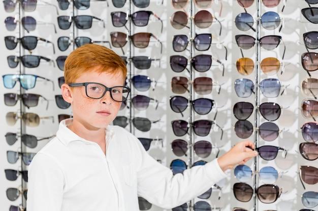 Niño inocente mirando a la cámara blanca con espectáculo en la tienda de óptica