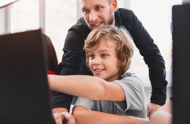 Niño inteligente feliz apuntando a la pantalla del portátil mientras se discute el proyecto con el maestro durante la lección de programación en el aula