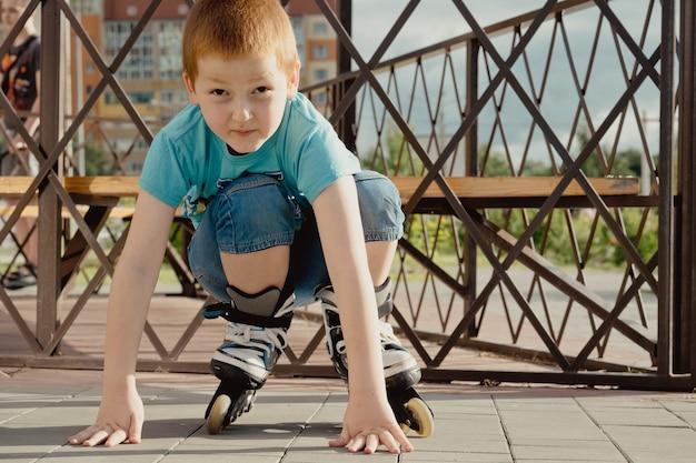 Un niño intenta levantarse del suelo después de caer con los patines. un niño en bicicleta o en patines, se cayó y se lastimó la pierna