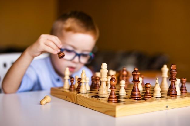 Niño jengibre con síndrome de down con anteojos grandes jugando ajedrez en casa
