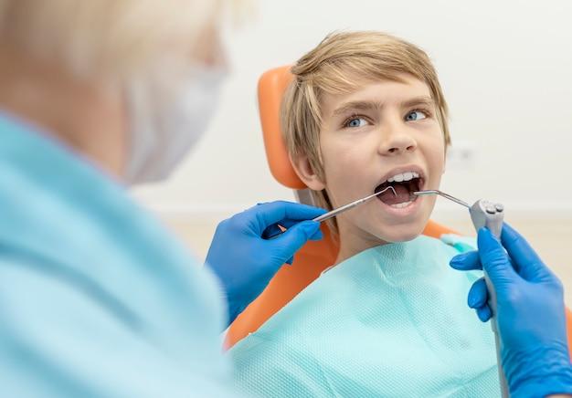 Niño con jeringa de agua pulverizada y sonda de dentista en la boca mirando al dentista