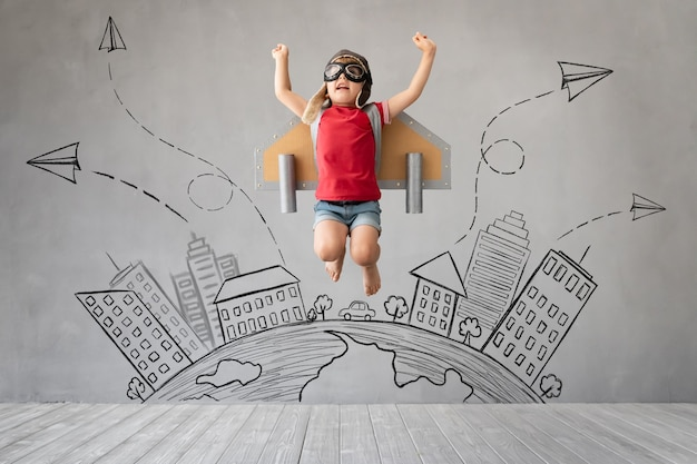 Niño con jetpack saltando contra la pared de hormigón gris.