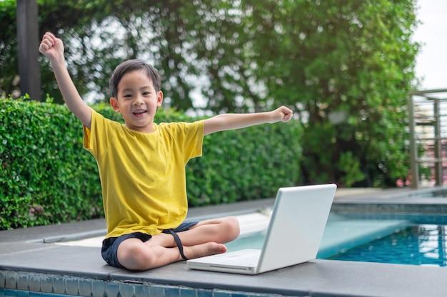 Niño joven asiático feliz que usa la computadora portátil con la mano para arriba en el lado de la piscina