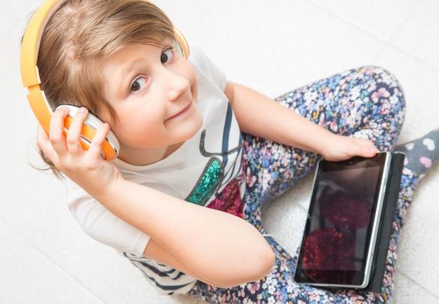 Niño joven está escuchando música con auriculares en tableta