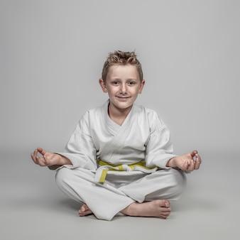 Niño joven, llevando, artes marciales, disfraz, meditar