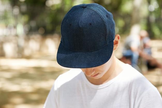 Niño joven, llevando, camiseta blanca, y, gorra, en el estacionamiento