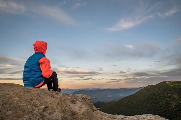 Niño joven muchacho caminante sentado en las montañas disfrutando de la vista del increíble paisaje de montaña.