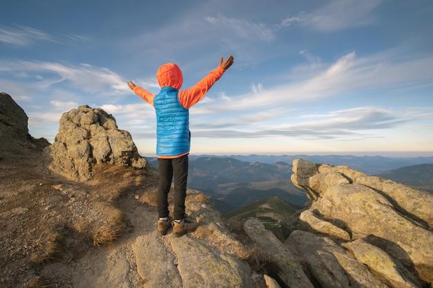 Niño joven muchacho excursionista de pie con las manos levantadas en las montañas disfrutando de la vista del increíble paisaje de montaña al atardecer.