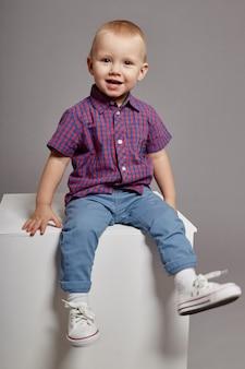 Niño joven sonriendo sentado en un cubo blanco