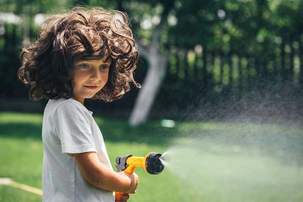 El niño juega con agua en el patio trasero del jardín.