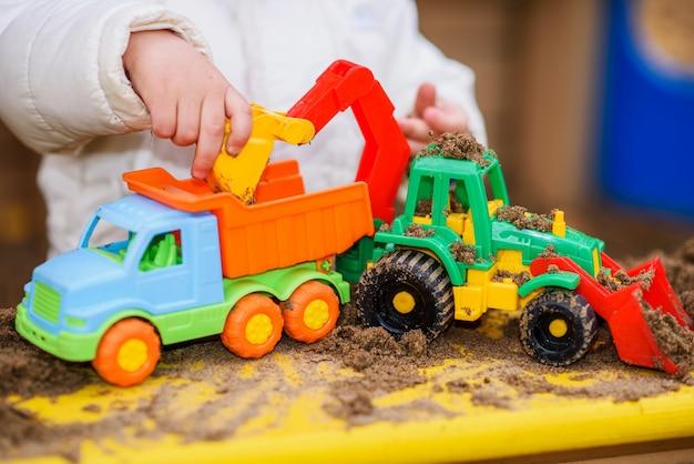 El niño juega autos en el patio de recreo