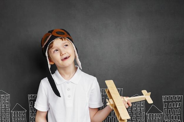 Niño juega con un avión de juguete en casa.