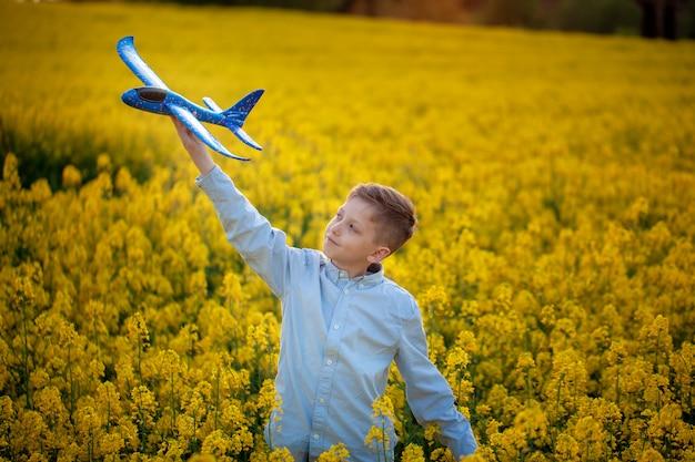 El niño juega con un avión de juguete en la puesta de sol y sueña con viajar en el día de verano.